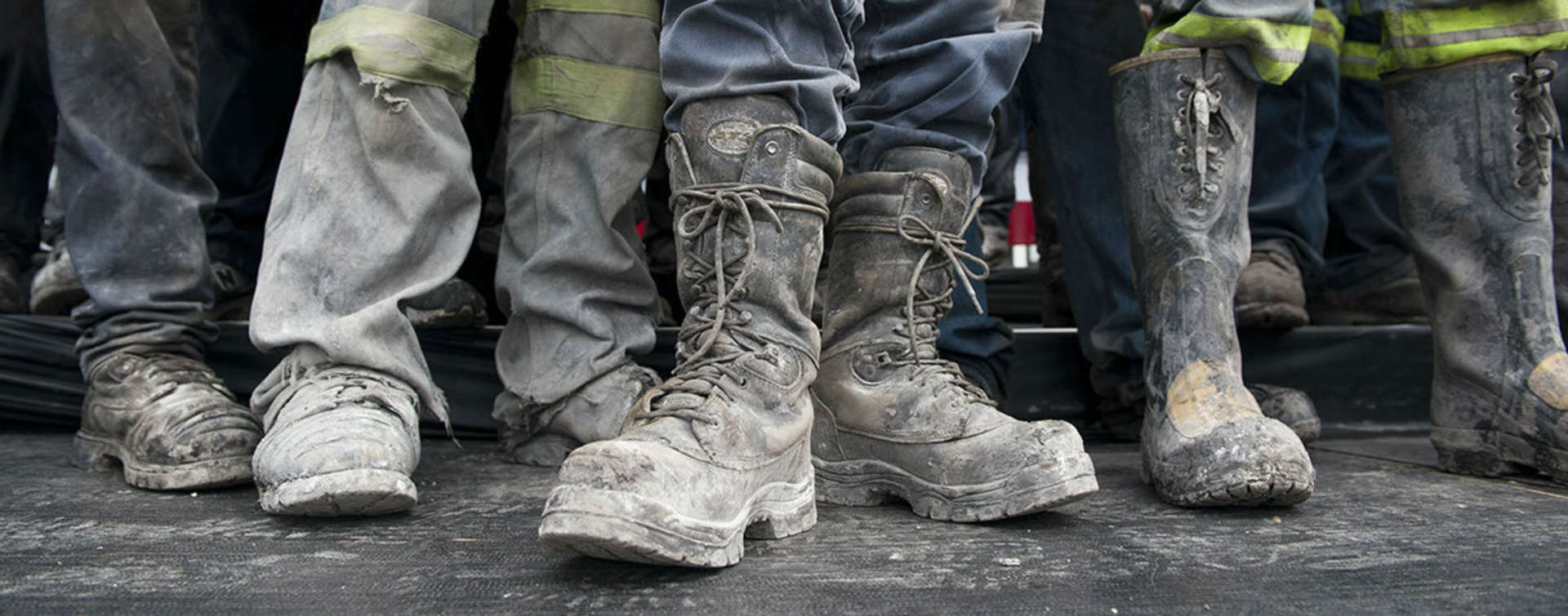 photo of construction workers feet in muddy boots